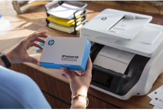 A woman opens up a HP Instant Ink Welcome Kit in front of a HP OficeJet Pro 8720 All-in-One Printer.