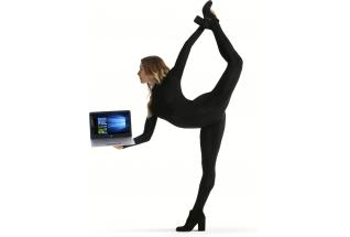 Dancer Allison Holker standing in scorpion pose, fholding the HP ENVY Notebook open with Windows 10