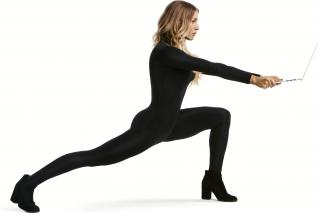 Dancer Allison Holker standing in lunge position, holding the HP ENVY Notebook