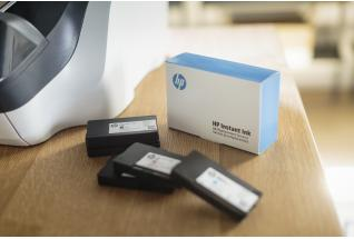 A HP OfficeJet Pro 8720 All-in-One Printer sitting next to a HP Instant Ink Welcome Kit on a desk.