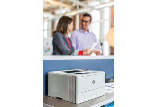 Man and woman stands over print station with a HP LaserJet Pro M402dn looking at Mono output