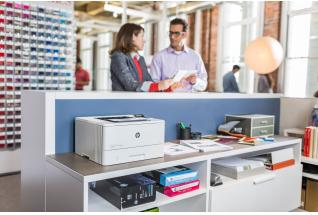 Man and woman stands over print station with a HP LaserJet Pro M402dn looking at Mono output in an o